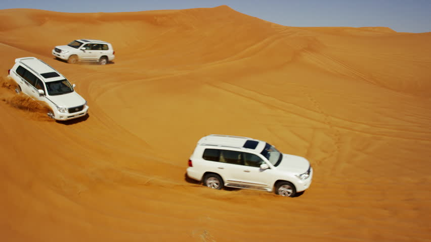 Dubai - April 2016: Aerial Drone Off road vehicles driving groups tourists across undulating desert sand dunes outside Dubai shot on RED DRAGON