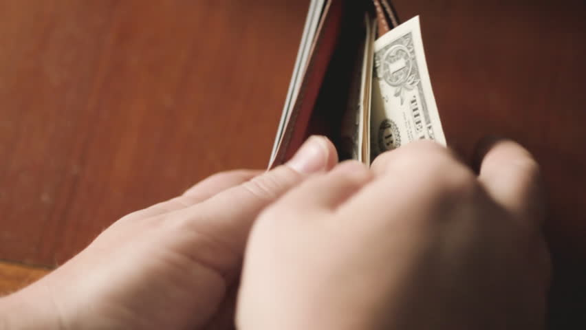 Man counting money in wallet
