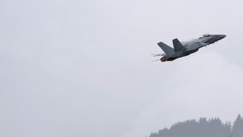 McDonnell Douglas F/A-18 of Swiss airforce do a looping in a bad weather day. McDonnell Douglas F/A-18 Hornet is a supersonic multirole combat aircraft. UltraHD 4K Video with original audio.