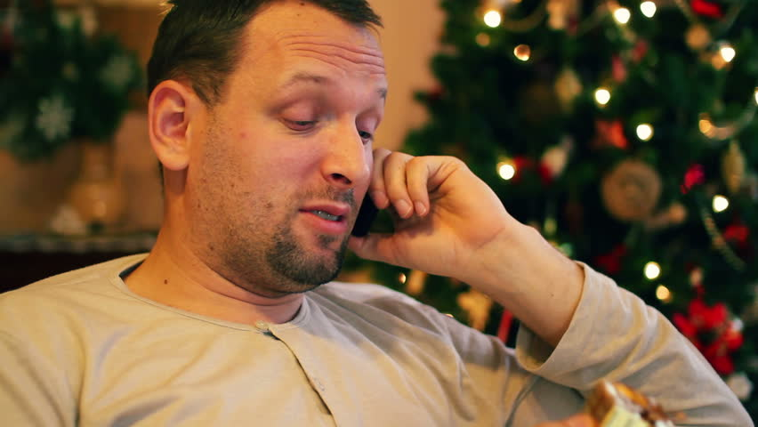Disappointed man with little gift talking on cellphone