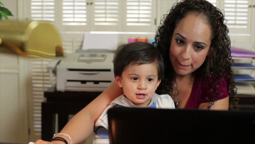 A pretty Hispanic mom in her home office shows her little son something on the laptop.