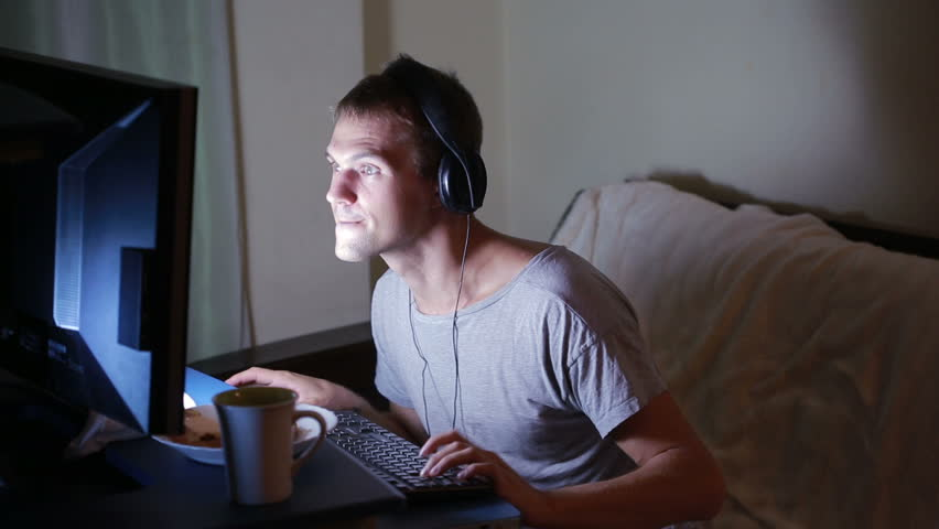 Man playing video games on your computer. late at night on the computer gamer