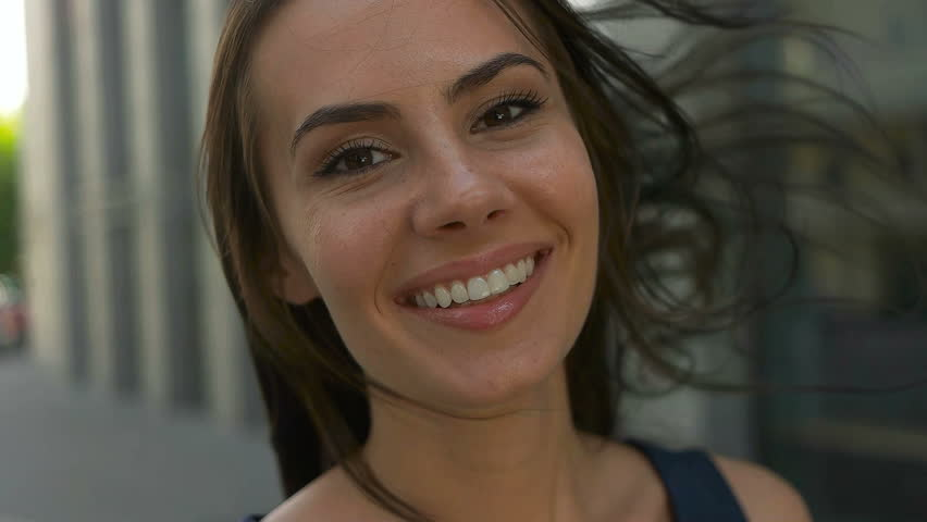 Wonderful smiling woman with a lovely look and natural make up looking at camera and the wind moving her hair | Shutterstock Video #18899135