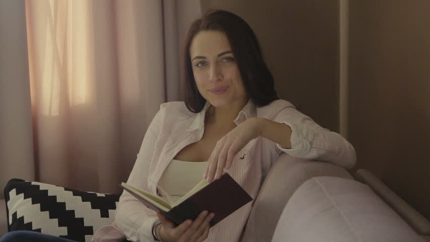Smiling beautiful brunette relaxing on the couch and reading a book, looking at camera in the living room | Shutterstock HD Video #18901565