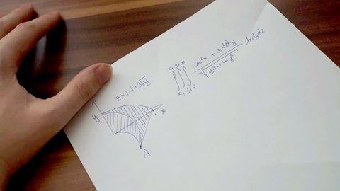 Student is writing on paper and solving difficult mathematical equation in math exam.