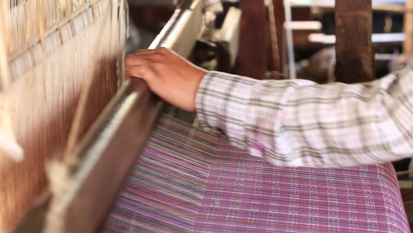 Traditional Burmese textile manufacture in craft village where old women work on wooden weaving loom machines and spin yarn creating silk or cotton fabric. Inle Lake, Myanmar. Burma