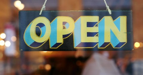 Open vintage wooden sign broad through the glass of store window.