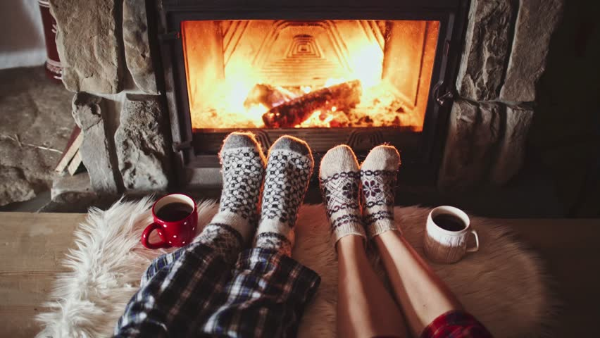 Couple Feet in Woollen Socks by the Cozy Fireplace, 4K. Man and Woman relax by warm fire and warming up their feet. Close up. Winter and Christmas holidays concept.  #18943325