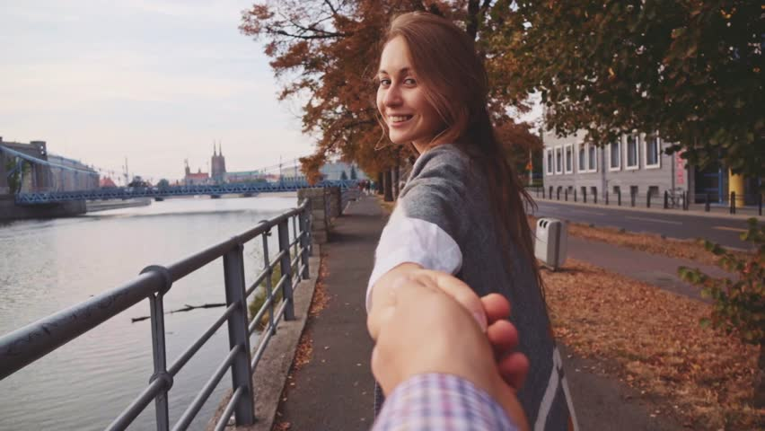 POINT OF VIEW: Young Woman Pulling her Boyfriend Through Autumn City Street. SLOW MOTION 120 fps. POV: Happy Girlfriend Makes her Man to Follow Her to the City Bridge.