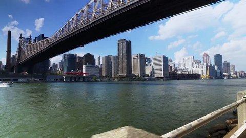 A daytime establishing shot of the Ed Koch Queensboro Bridge between Manhattan and Brooklyn as a speed boat passes underneath.