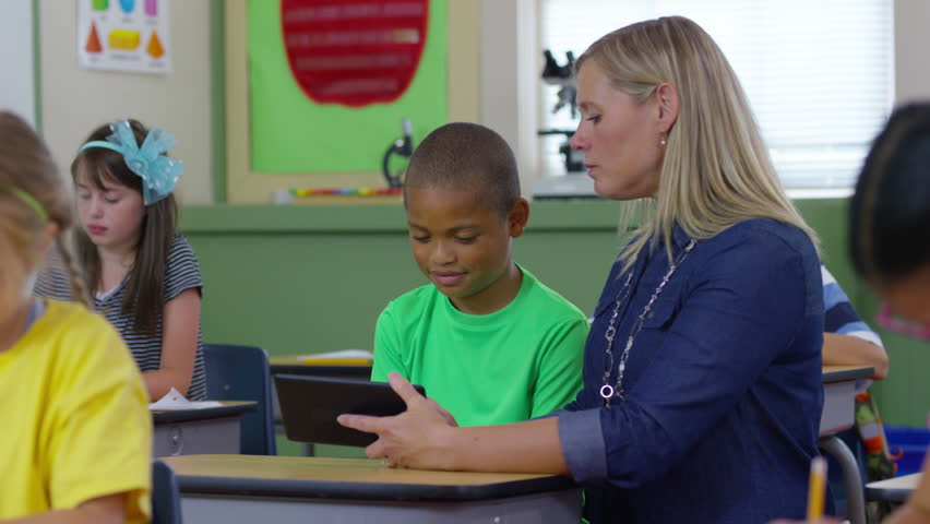 Teacher and student look at digital tablet in school classroom | Shutterstock HD Video #19004095