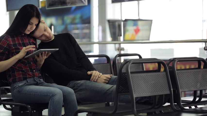 Young couple is sitting in airport waiting area. | Shutterstock HD Video #19006975
