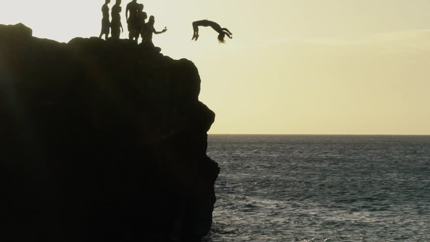 Silhouette of a man jumping off a cliff into the water, slow motion   Shutterstock HD Video #19033645