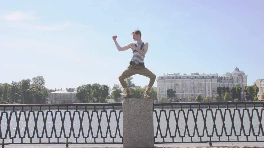Man in marine shirt, military pants dance electro, staying on postament at seafront. Surrealism. Water, summer sunny day