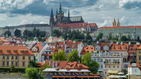 Charles Bridge and Prague Castle timelapse, view from embankment with vltava river, Czech Republic. Cloudy sky at sunny day