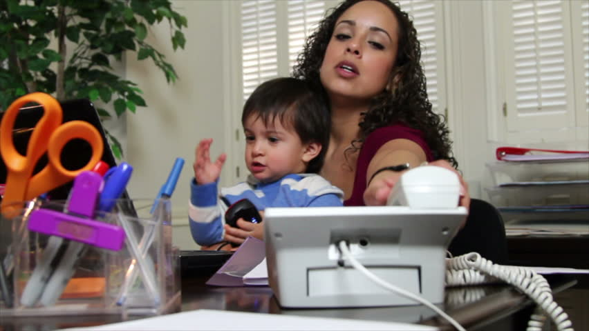 A pretty Hispanic mom in her home office trying to get her work done while her little son sits in her lap.