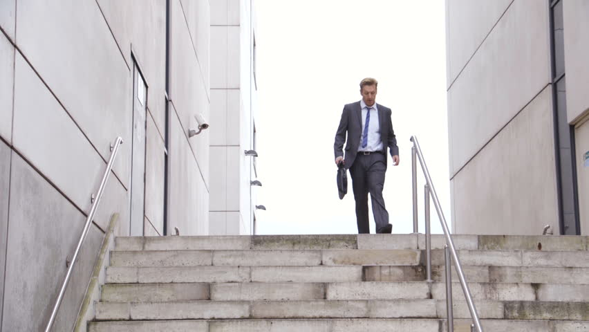 Businessman late for work in the city. He is wearing a suit and carrying a briefcase. He runs down some stairs and out of the frame. | Shutterstock HD Video #19064875