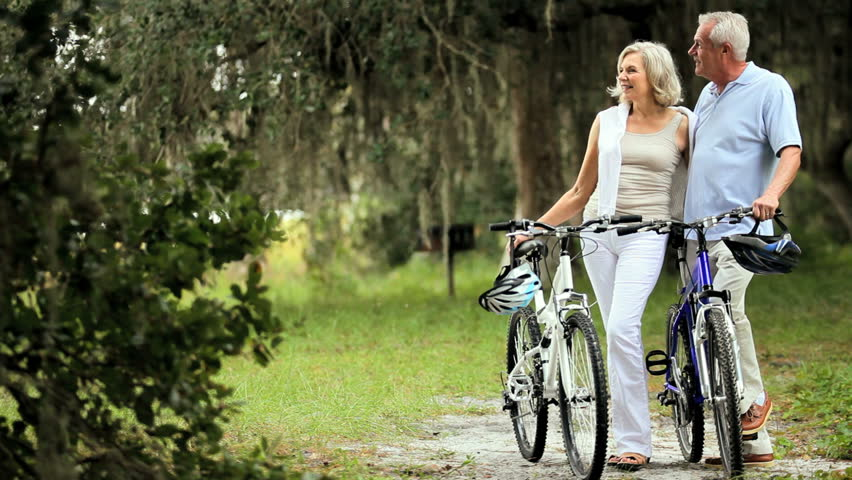 Active mature couple enjoying their retirement lifestyle out cycling
