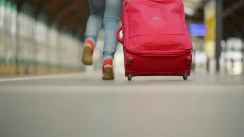 Girl Running with a suitcase in a train station