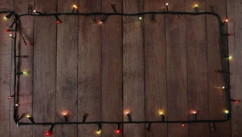 Christmas colorful lights frame on wooden table, frame background