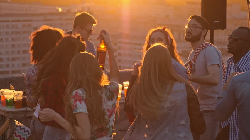 Group of multi-ethnic young people drinking beer, dancing to the music played by dj and raising their arms up in the air at sunset party on city rooftop