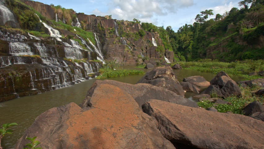 Camera moves from large brown stones on foreground to wide stormy waterfall cascade Panagarh in Vietnam | Shutterstock HD Video #19086205