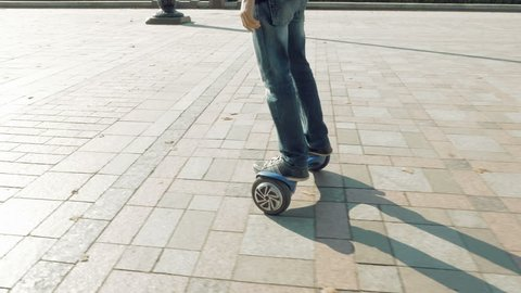 Man is riding hoverboard or electric self balancing gyro scooter board on the side walk. Modern and trendy urban transportation gadget. Popular city futuristic device among young people.
