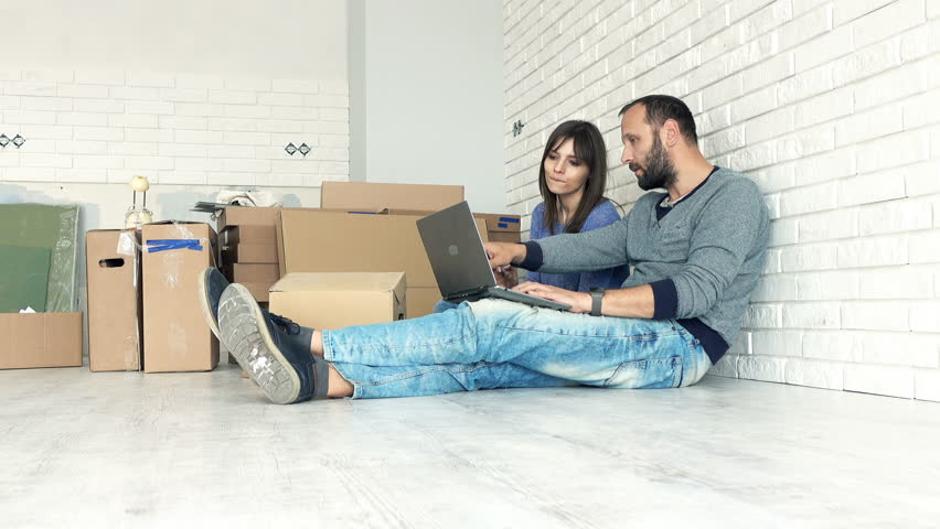 Young couple with tablet and laptop talking about new home project on floor   | Shutterstock HD Video #19112275