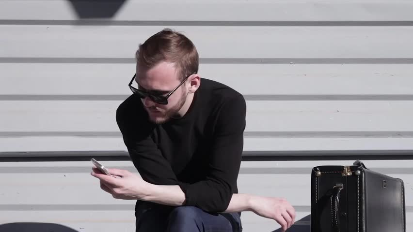 Cinemagraph - a Young Pretty Man is Typing on the Smartphone Froze Body Moves Hand Loop