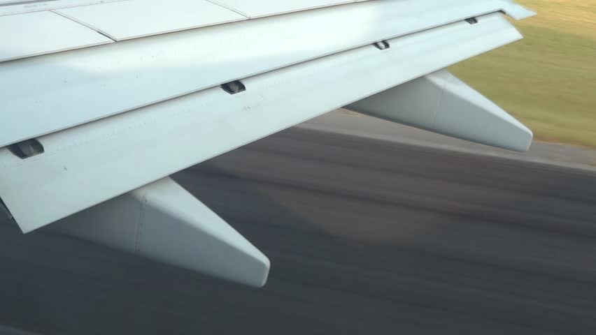 Aircraft taking off the runway. Filmed from  commercial jet airplane window.