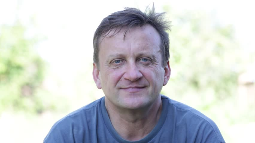 Portrait of middle-aged man relaxing in nature, close up