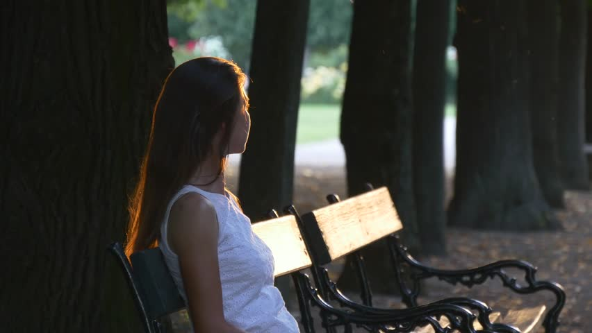 Young woman sitting on a bench in the park and looks toward the setting sun, which with its rays illuminates a woman and bench | Shutterstock HD Video #19136665