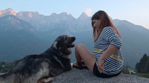 A gril playing with her dog on a mountain