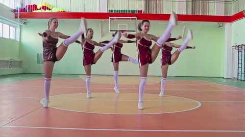 Slow motion video of cheerleading practice, group of beautiful girls performing cabaret jumping and stopping in formation looking at camera with hands in air in school gymnasium