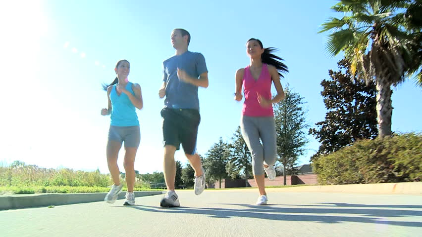 Young multi ethnic friends keeping to a fitness program together jogging outdoors