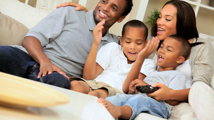 Young ethnic family sitting together on sofa watching television