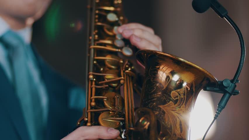 Saxophonist play on golden saxophone. Live performance. Jazz artist. Spotlights. Microphone