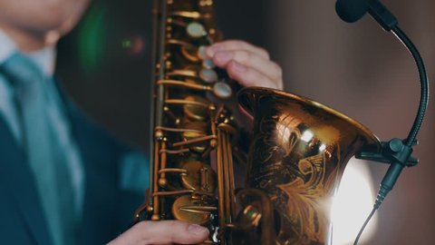 Saxophonist play on golden saxophone. Live performance. Jazz artist. Spotlights. Microphone