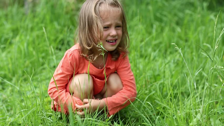 Little girl in red dress crying, because she got burnt with nettle. True sincere weeping and emotions of little girl. Little girl sits on grass and crying. Real situation, pain caused by chemical burn