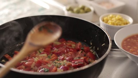 Mediterranean food: cooking fresh pachino tomatoes to season pasta, close-up
