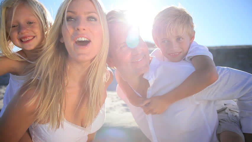 Young blonde caucasian parents having fun with their children on the beach