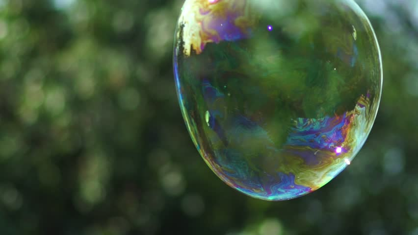 Metamorphosis of big soap Bubbles in Slow Motion. Close up view of beautiful big soap bubble is flying near the trees at sunny day. Big bubble shimmering colors of the rainbow.