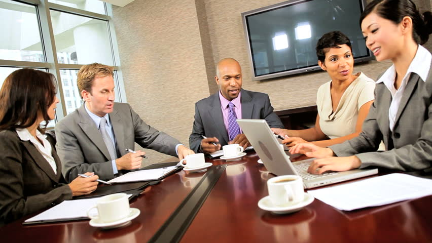 Team of five multi ethnic executives in city clothes meeting in a modern office boardroom | Shutterstock HD Video #1924615