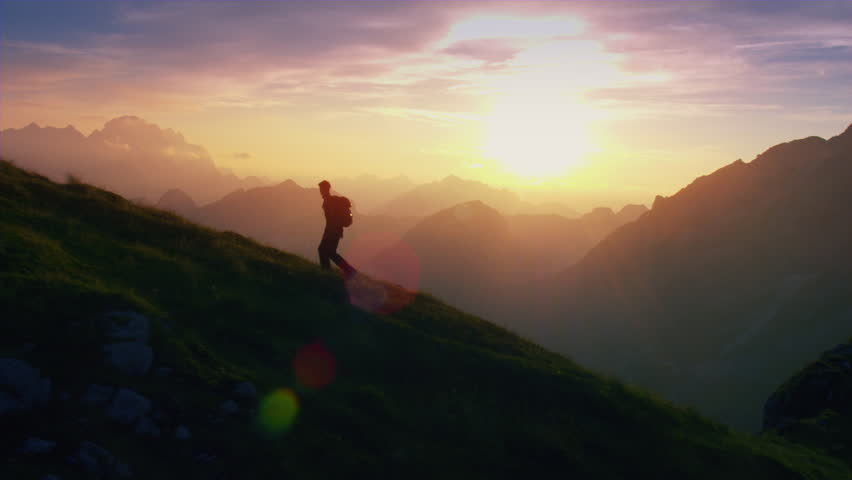 Aerial, edited - Epic shot of a man hiking on the edge of the mountain as a silhouette in colorful sunset
