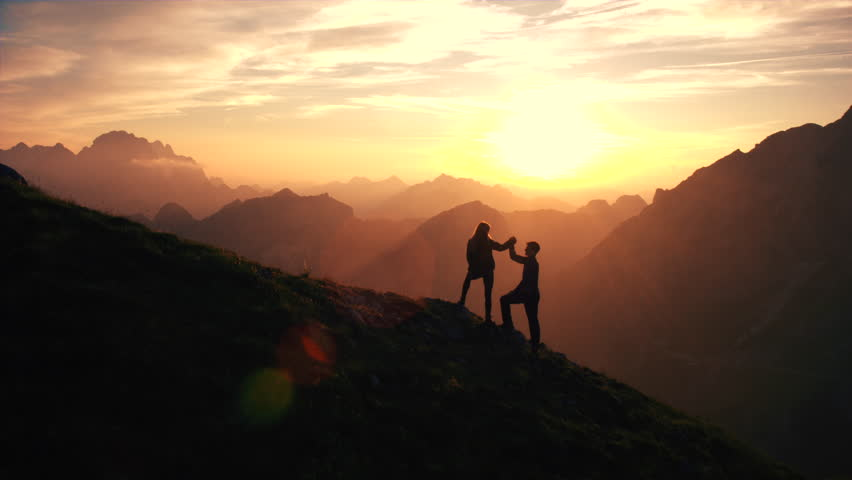 Aerial, edited - Silhouette of a couple giving each other a high five celebrating successful climb on the mountain in beautiful sunset #19249195