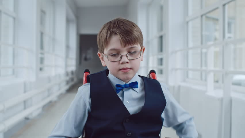 Handheld dolly-like shot of concentrated handicapped schoolboy in wheelchair wearing uniform and glasses riding along school hallway during recess