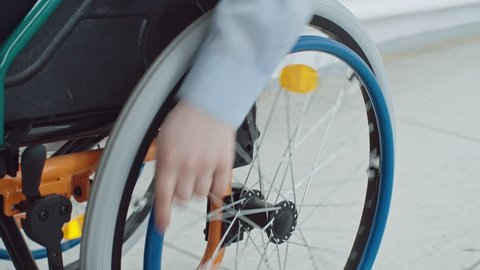 Closeup of little boys hand turning wheels on his wheelchair and riding along hallway