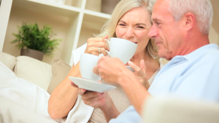 Senior couple in close up drinking coffee and laughing on their home sofa