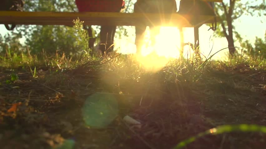 Beautiful happy young couple sitting on the bench in sunny park and making heart gesture together. Girlfriend and boyfriend in love, romantic date. Slow motion 240 fps high speed camera. Full HD 1080p