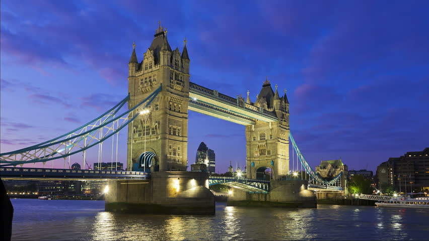 Tower Bridge in London at night being open  for passing underneath boat, London, United Kingdom. Time lapse footage of boat on Thames River with City of London lights in the background. | Shutterstock HD Video #1927135